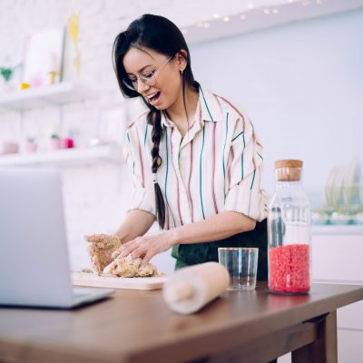 Cheerful young housewife in striped shirt and glasses with braid concentrated on cooking homemade bakery food at modern cozy kitchen
